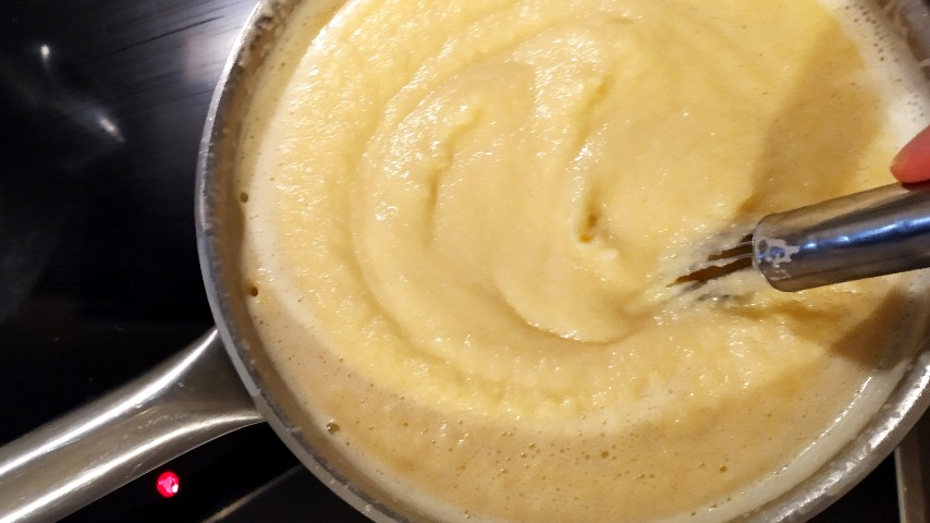 The semolina custard reaching the right consistency in a saucepan