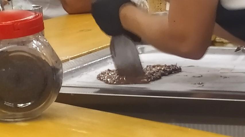 Η υπάλληλος κόβει το μίγμα με τις σπάτουλες