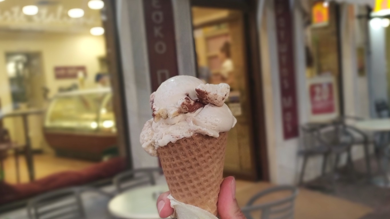 Hand holding a cone with a scoop of the tiramisu flavor from Arte Italiana, in front of the store