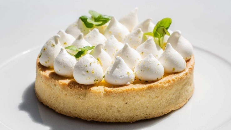 Lemon tart with meringue on a white plate by Christelle Brua from the Café Le Procope