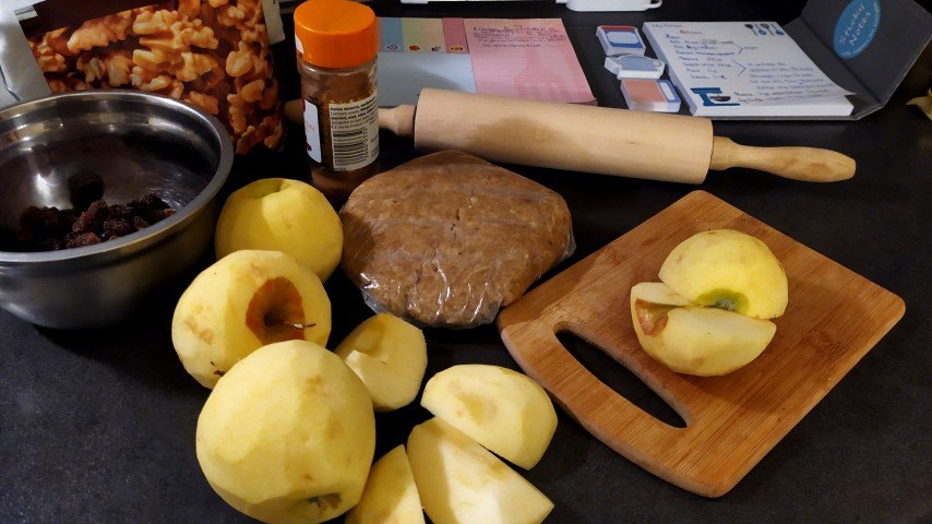 Peeled apples, a wooden cutting board, a package of walnuts, a bowl of raisins, a jar of cinnamon and a notepad on a kitchen's bench
