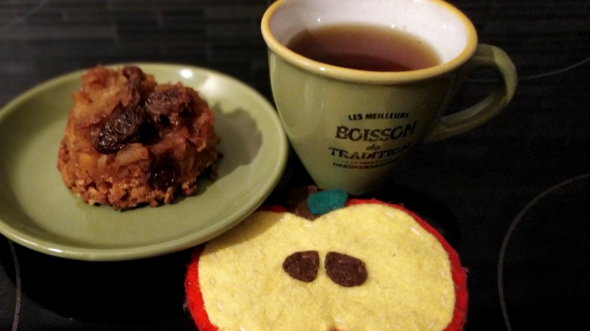 A tart Tatini, a small cup of tea and a handmade apple-shaped felt coaster.