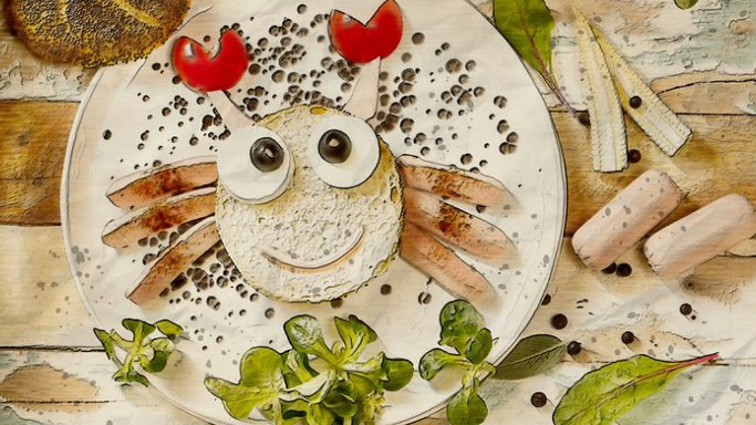 Photo of a healthy plate with vegetables shaped like a smiling crab