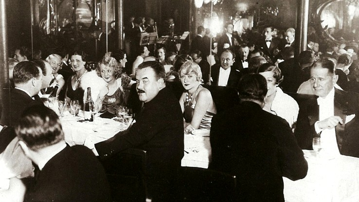 Old photograph of the busy Maxim's restaurant in Paris with tables full of people