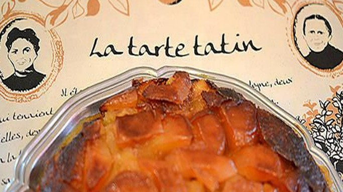 Coaster with the Tatin sisters and the title tarte Tatin on the top side, with a tart on top