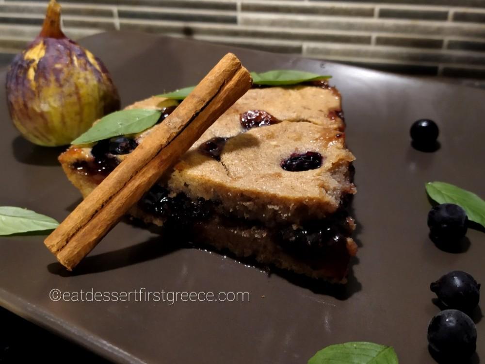 Κομμάτι Linzer torte, ένα στικ κανέλας, ένα σύκο, μερικά φραγκοστάφυλα και φύλλα βασιλικού σε καφέ ορθογώνιο πιάτο