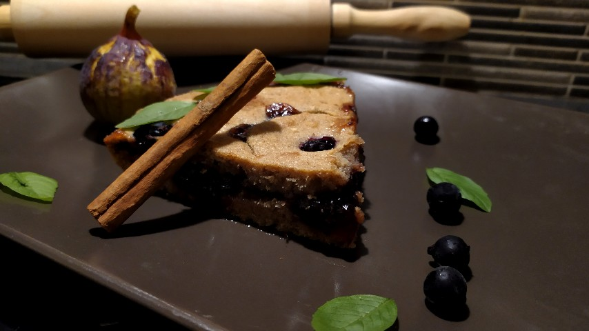 Α piece of Linzer torte, a fig, some blackberries and basil leaves on a rectangular brown plate, with a wooden rolling pin in the background