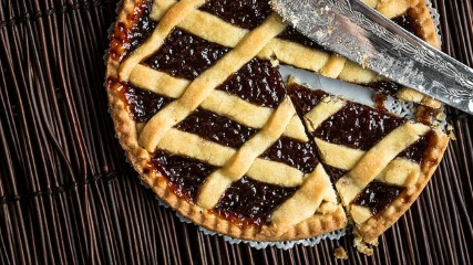 A pan with a jam tart, with a cut piece and a knife