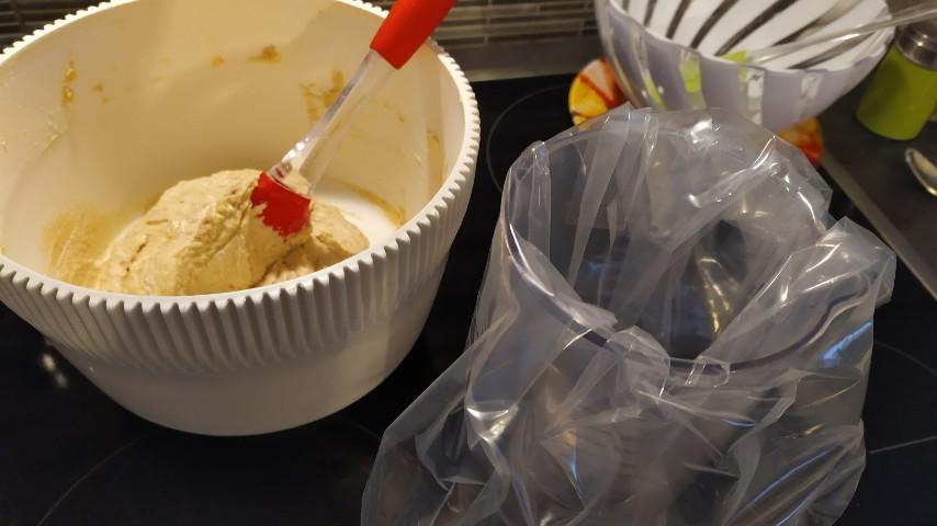 Μπωλ με την έτοιμη ζύμη και μια σπάτουλα σιλικόνης και δίπλα ένα δοχείο με μια σακούλα τροφίμων μέσα