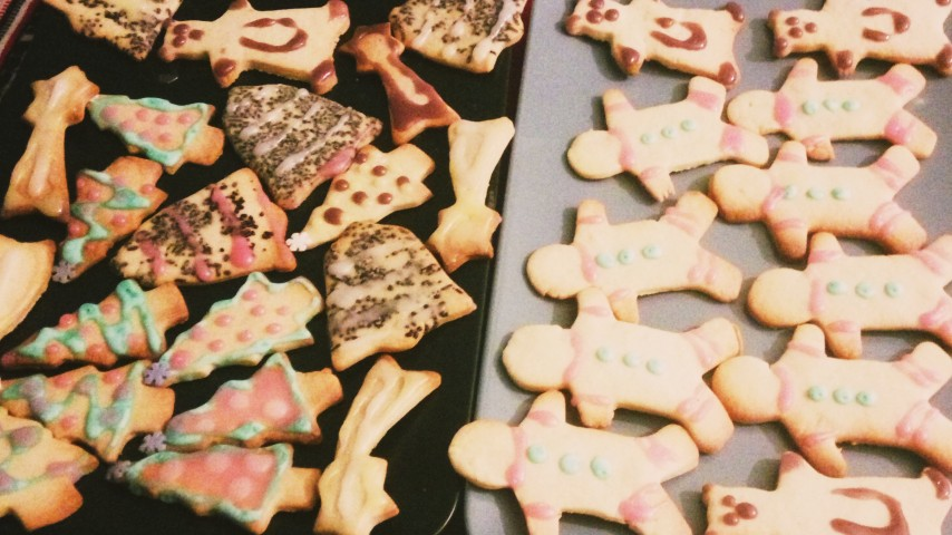 A black and a blue plate with Christmas cookies in various shapes