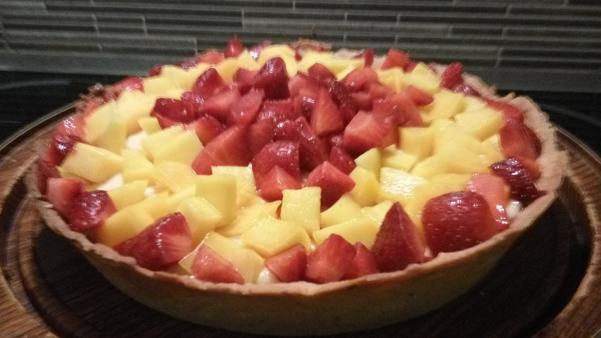 A tart with mango and strawberries on a wooden plate